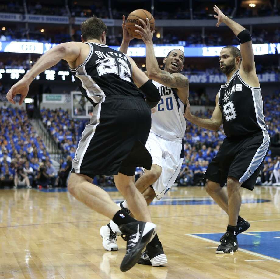 Dallas Mavericks' Devin Harris drives the ball between San Antonio Spurs' Tiago Splitter, left, and Tony Parker during the first half of game six in the first round of the Western Conference Playoffs at the American Airlines Center in Dallas, Friday, May 2, 2014. Photo: San Antonio Express-News