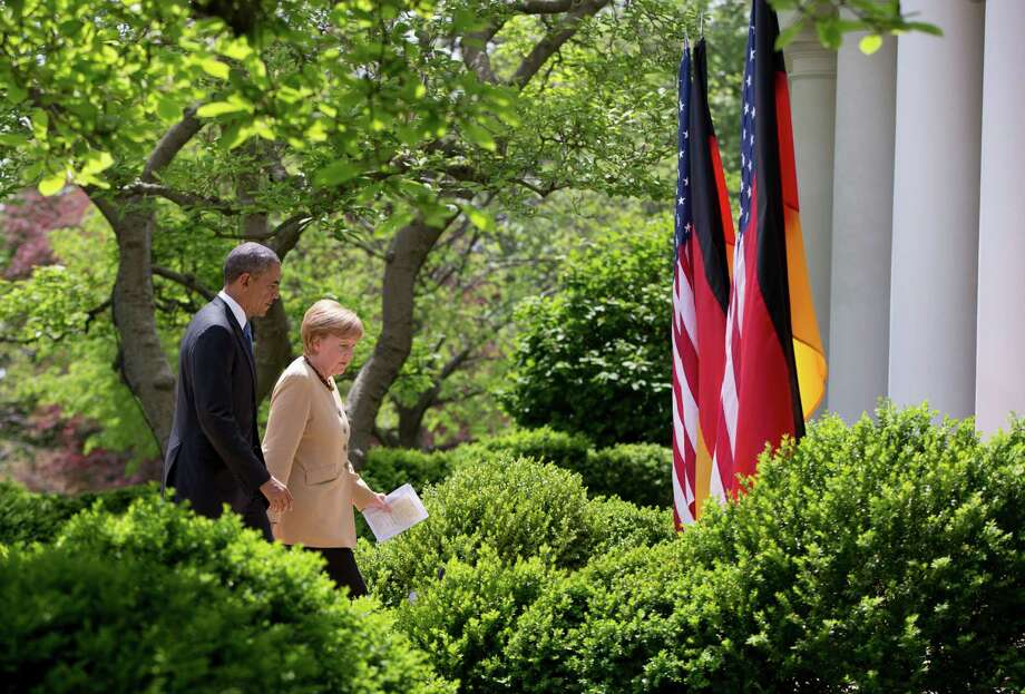 President Barack Obama and German Chancellor Angela Merkel walk to the Oval Office of the White House in Washington, Friday, May 1, 2014, after their joint news conference in the Rose Garden. Obama and Merkel are putting on a display of trans-Atlantic unity against an assertive Russia, even as sanctions imposed by Western allies seem to be doing little to change Russian President Vladimir Putin's reasoning on Ukraine. (AP Photo/Carolyn Kaster) Photo: Carolyn Kaster, STF / AP