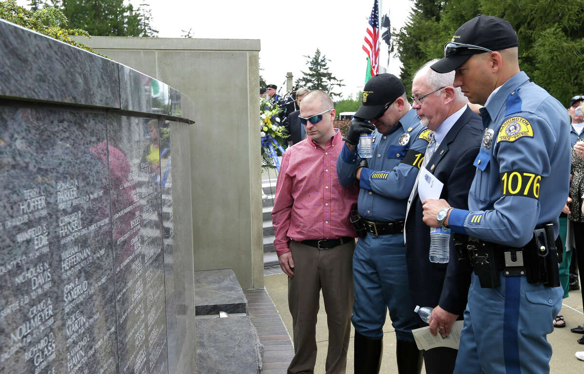 Sean O'Connell Sr., second from right, views the name of his son, Washington State Patrol Trooper Sean O'Connell Jr., on a granite wall of the Washington State Law Enforcement Officers Memorial following the annual law enforcement medal of honor ceremony, Friday, May 2, 2014 at the Capitol in Olympia, Wash. O'Connell Jr., who was among those honored at the ceremony, was killed May 31, 2013 in a motorcycle accident while he was helping with a traffic detour around the collapsed Skagit River Bridge. Also viewing the names are family friend, Neil Rappaport, left, and troopers Deion Glover, right, and Lance Ramsey, second from left.