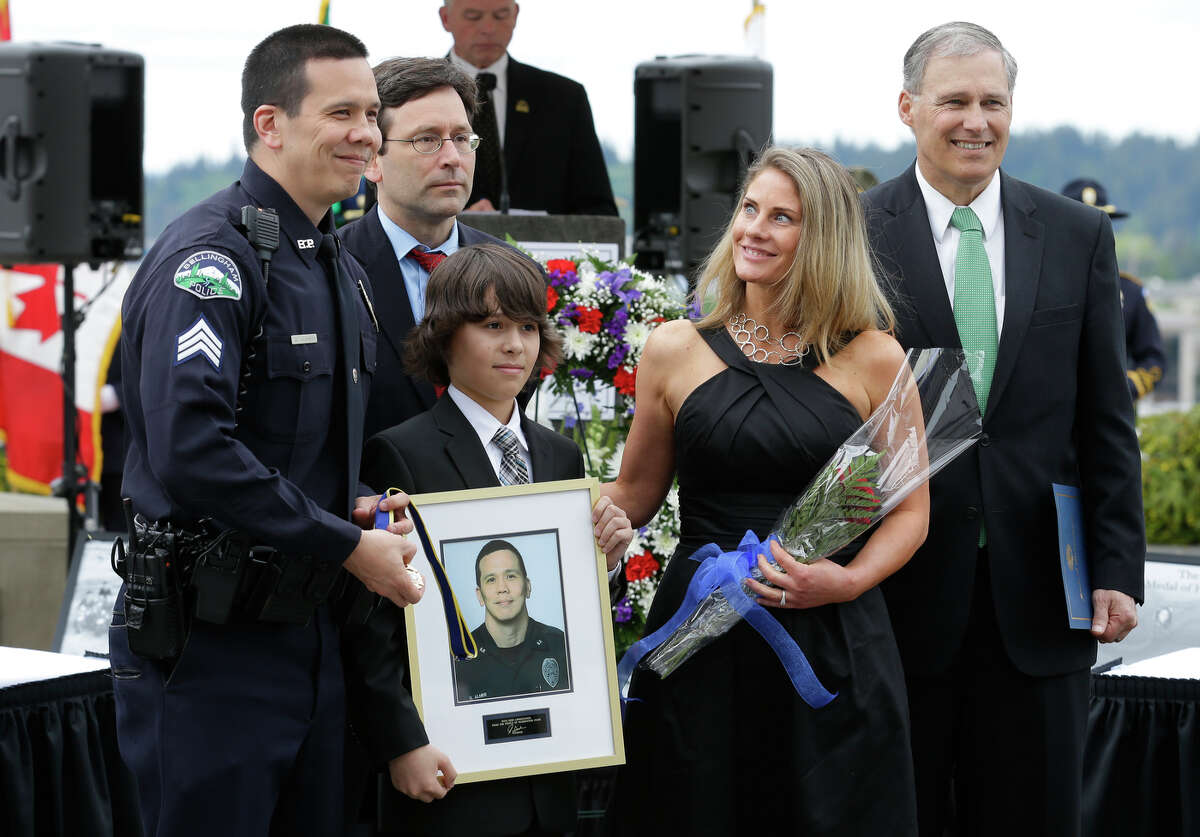 Bellingham Police Sgt. Donald Almer, left, stands with his son Dawson and his wife Laura after he was given the law enforcement medal of honor by Gov. Jay Inslee, right, and Attorney General Bob Ferguson, second from left, Friday, May 2, 2014 during a ceremony at the Capitol in Olympia, Wash. Almer was honored for his actions in stopping an armed robbery suspect vehicle in 2013.