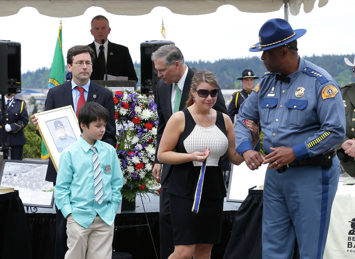 Washington State Patrol Chief John Batiste, right, escorts Alissa O'Connell, second from right, and her son Kian, 8, lower left, after O'Connell was given a state law enforcement medal of honor by Gov. Jay Inslee, third from right, and Attorney General Bob Ferguson, upper left, on behalf of her husband, Trooper Sean O'Connell Jr., lower right, who was killed May 31, 2013, in a motorcycle accident while he was helping with a traffic detour around the collapsed Skagit River Bridge, during the annual law enforcement medal of honor ceremony, Friday, May 2, 2014 at the Capitol in Olympia, Wash.