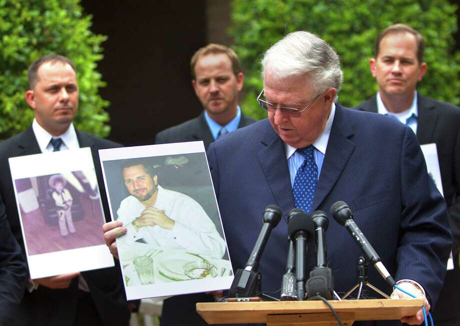 A lawyer for Doug Lewis - pictured holding a photo of his son, Jason Lewis - said the body had bruising consistent with marks left by boots and batons. Photo: Cody Duty, Staff / © 2014 Houston Chronicle