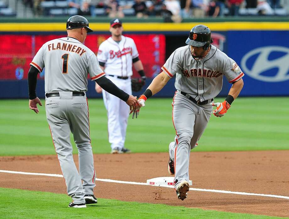 Third-base coach Tim Flannery greets Angel Pagan, who homered on the game's second pitch. Photo: Scott Cunningham, Getty Images