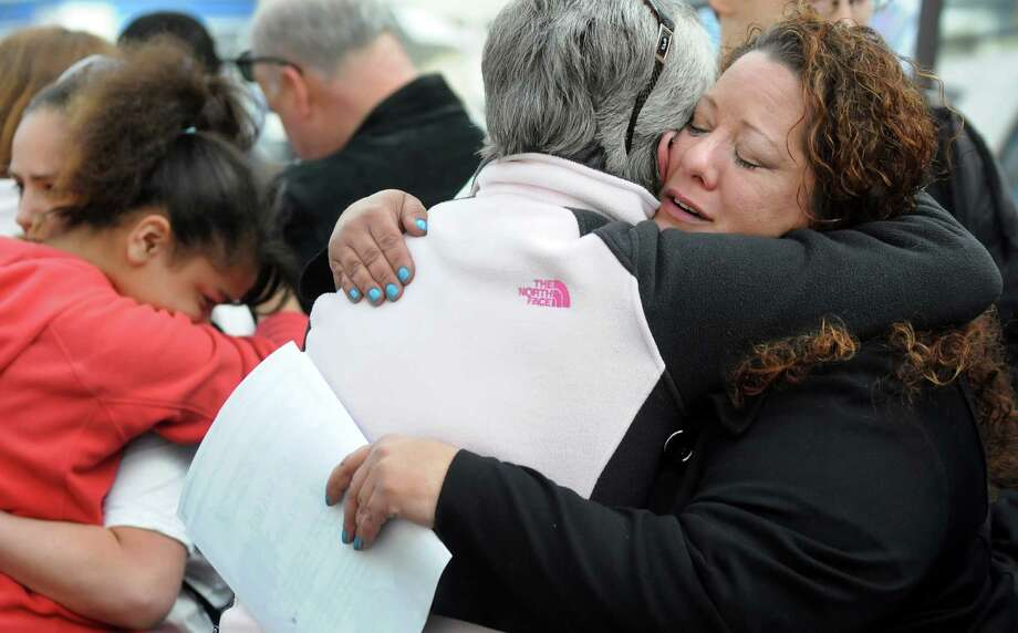 Elizabeth Dolder, sister to Dave Terry, right, receives condolences on the one-year anniversary of her brother's death on Friday, May 2, 2014, in Schenectady, N.Y. Terry and three of his children perished, and another remains in serious condition, during a house fire on Hulett Street. (Cindy Schultz / Times Union) Photo: Cindy Schultz / 00026725A
