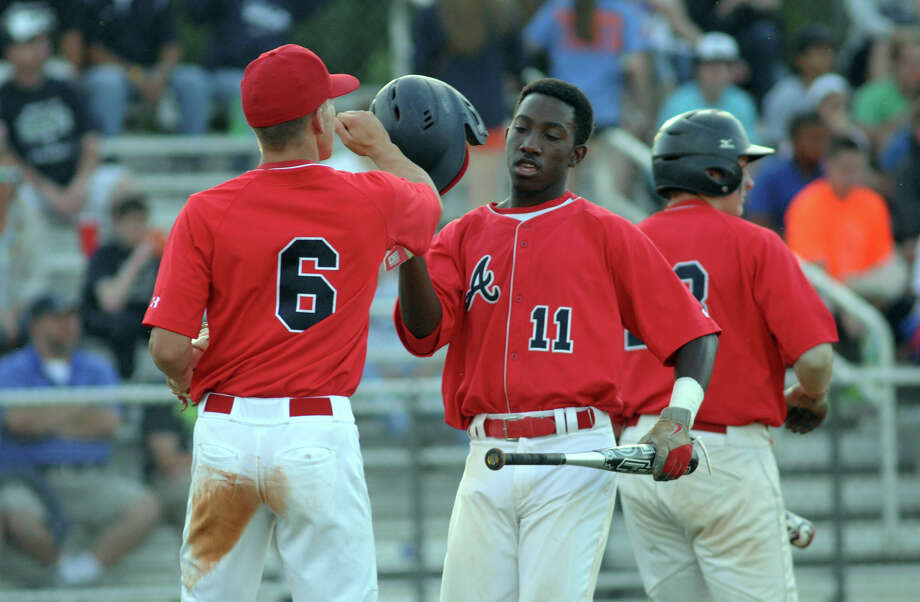 Atascocita baserunner Joseph Anderson (#11) is greeted at home plate by teammate Ryan Wadkins (#6) after scoring in the top of the first inning against College Park during their playoff game at College Park High School on Friday. Photo: Jerry Baker, For The Chronicle