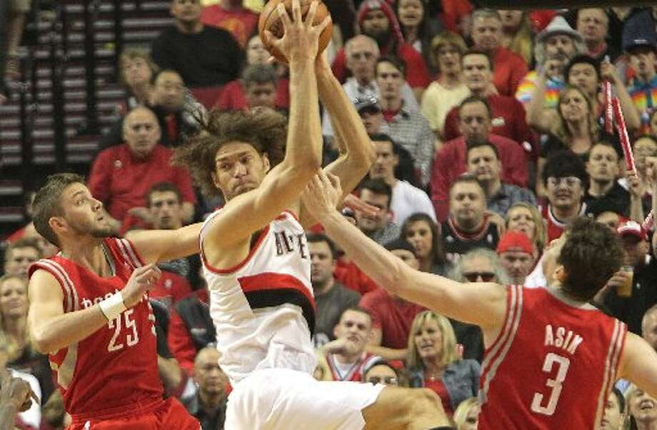 Trail Blazers center Robin Lopez (42) grabs a rebound away from Rockets forward Chandler Parsons (25) and center Omer Asik (3) during the first quarter. Photo: James Nielsen, Houston Chronicle