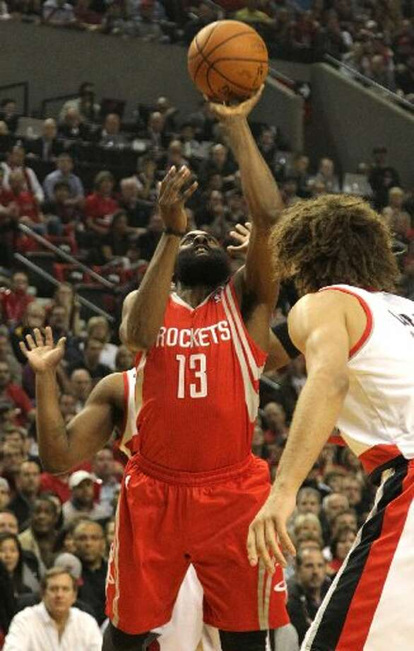 Rockets guard James Harden takes a shot over Portland Trail Blazers center Robin Lopez during the first quarter. Photo: James Nielsen, Houston Chronicle