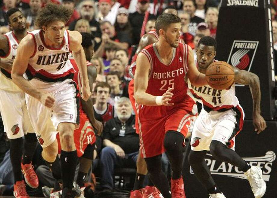 Rockets forward Chandler Parsons (25) runs the ball up court with Portland Trail Blazers center Robin Lopez (42) and forward Thomas Robinson (41) giving chase during the second quarter. Photo: James Nielsen, Houston Chronicle