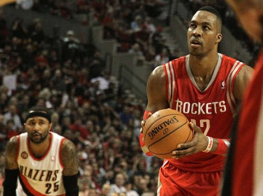 Rockets center Dwight Howard (12) shoots a free throw with Portland Trail Blazers guard Mo Williams (25) looking on during the second quarter. Photo: James Nielsen, Houston Chronicle