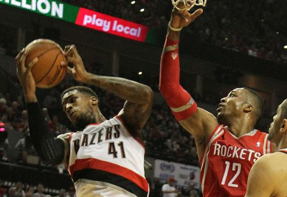 Trail Blazers forward Thomas Robinson (41) pulls down a rebound against Houston Rockets center Dwight Howard (12) during the second quarter. Photo: James Nielsen, Houston Chronicle