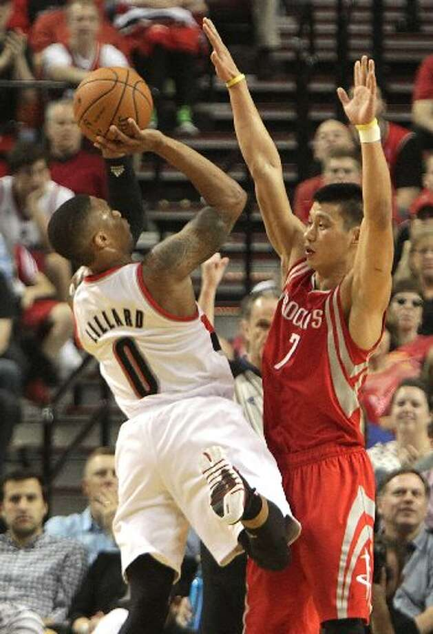 Rockets guard Jeremy Lin (7) defends a shot by Portland Trail Blazers guard Damian Lillard (0) during the first quarter. Photo: James Nielsen, Houston Chronicle