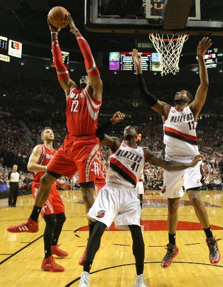 Rockets center Dwight Howard (12) grabs a rebound away from Portland Trail Blazers forward Thomas Robinson (41) and forward LaMarcus Aldridge (12) during the first quarter. Photo: James Nielsen, Houston Chronicle