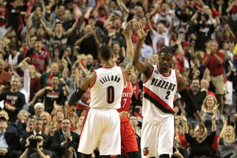 Trail Blazers guard Wesley Matthews (2) and Portland Trail Blazers guard Damian Lillard (0) high five during the first quarter. Photo: James Nielsen, Houston Chronicle