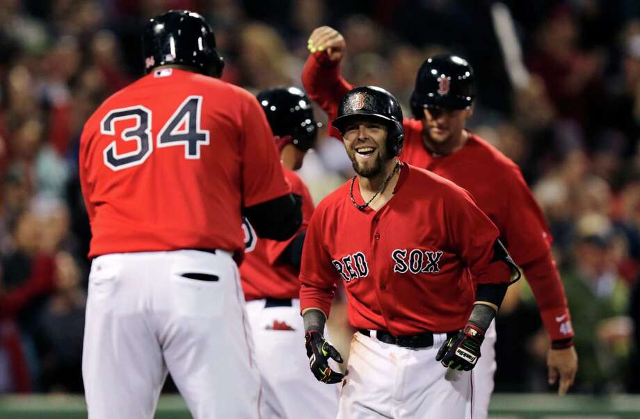 Boston Red Sox's Dustin Pedroia smiles as he is congratulated by teammate David Ortiz (34) after his grand slam off Oakland Athletics pitcher Ryan Cook during the sixth inning of a baseball game at Fenway Park in Boston, Friday, May 2, 2014. (AP Photo/Charles Krupa) ORG XMIT: MACK111 Photo: Charles Krupa / AP