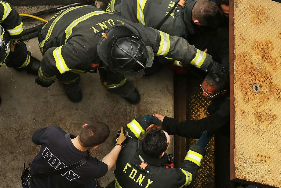 NEW YORK, NY - MAY 02: New York City firefighters  use an emergency staircase to evacuate passengers from a derailed F train on May 2, 2014 in the Woodside neighborhood of the Queens borough of New York City. According to the Metropolitan Transportation Authority  (MTA) the express F train was bound for Manhattan and Brooklyn when it derailed at 10:40 a.m. about 1,200 feet from the 65th station in Woodside, Queens with hundreds of passengers on board. (Photo by Spencer Platt/Getty Images) Photo: Spencer Platt, Getty Images