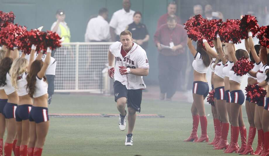 J.J. Watt runs down the line of Texans cheerleaders during player introductions for the 2014 J.J. Watt Charity Classic on Friday at Constellation Field in Sugar Land. Photo: Karen Warren, Houston Chronicle