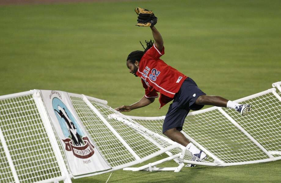 Keshawn Martin falls into the outfield fence as he caught a near home run ball hit by A.J. Bouye during the softball game. Photo: Karen Warren, Houston Chronicle