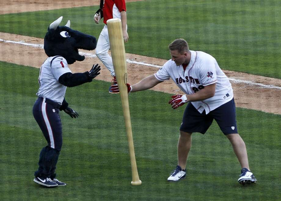 J.J. Watt grabs a big bat from Toro during the softball game. Photo: Karen Warren, Houston Chronicle