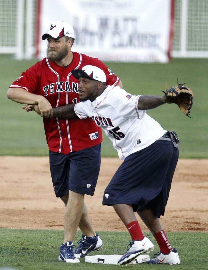 J.J. Watt grabs a big bat from Toro during the softball game. Photo: Karen Warren, Houston Chronicle