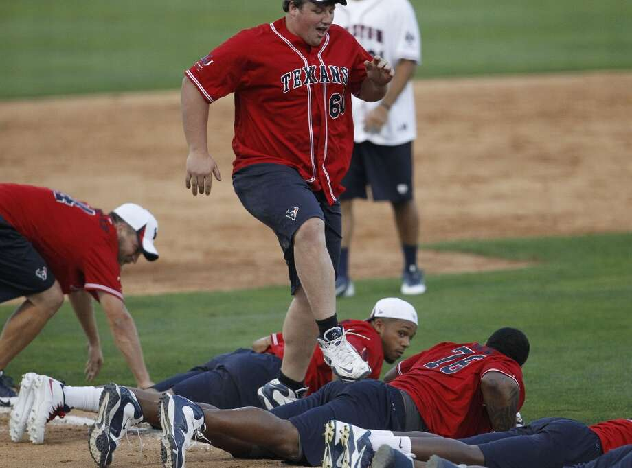 Ben Jones jumps over teammates on his way home after a home run during the softball game. Photo: Karen Warren, Houston Chronicle