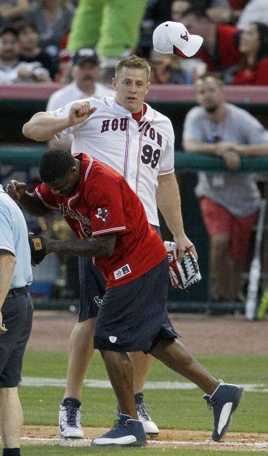 J.J. Watt knocks Andre Johnson's cap off during the softball game. Photo: Karen Warren, Houston Chronicle