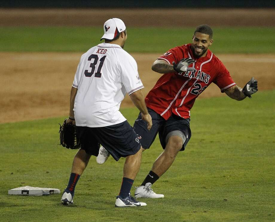 Arian Foster smiles as he rounds second base and Shiloh Keo during the softball game. Photo: Karen Warren, Houston Chronicle