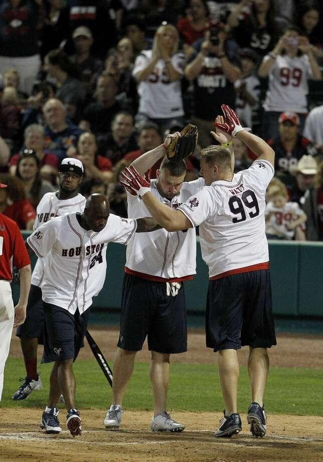 J.J. Watt celebrates his home run with teammates during the softball game. Photo: Karen Warren, Houston Chronicle
