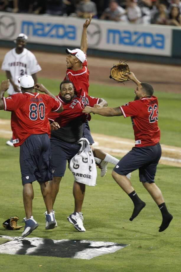 Andre Johnson and Arian Foster celebrates with their teammates after beating J.J. Watt's team during the softball game. Photo: Karen Warren, Houston Chronicle