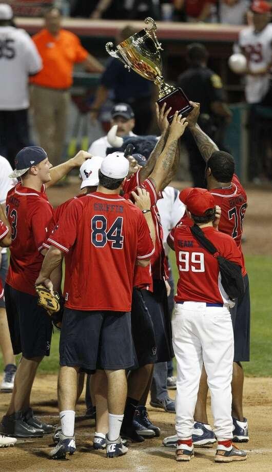 Team Offense celebrate after beating J.J. Watt's defensive team during the softball game. Photo: Karen Warren, Houston Chronicle