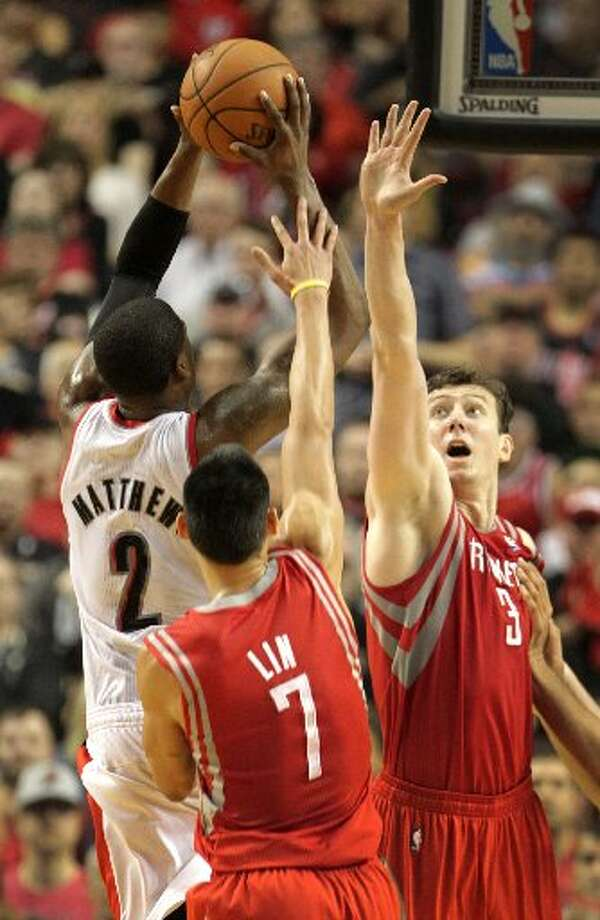 Trail Blazers guard Wesley Matthews (2) takes a shot against Houston Rockets center Omer Asik (3) and guard Jeremy Lin (7) during the second quarter. Photo: James Nielsen, Houston Chronicle