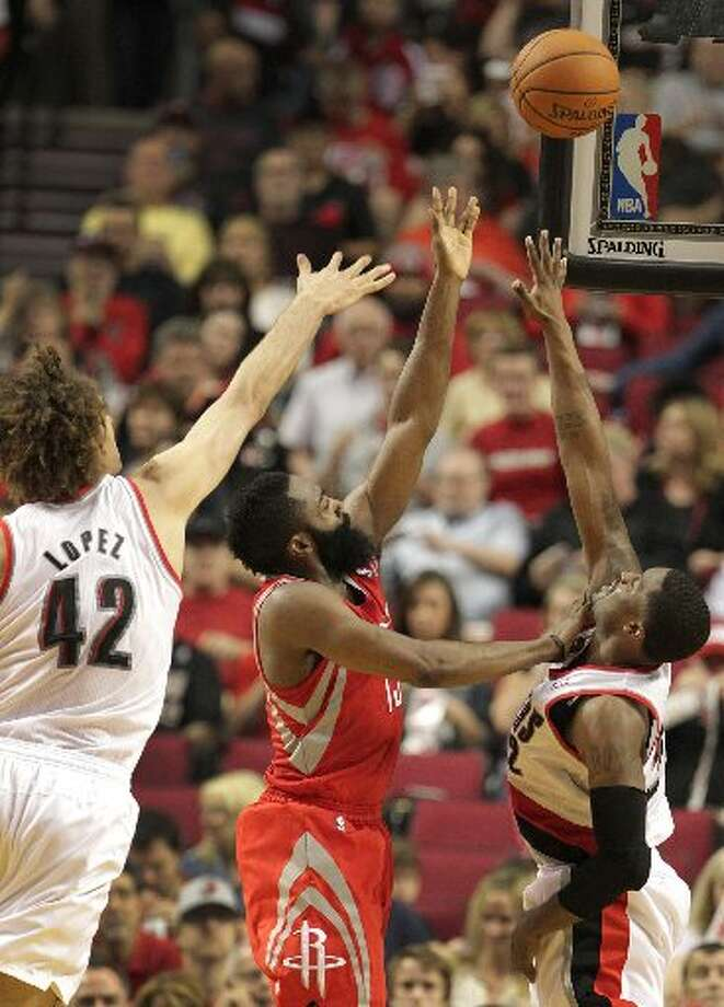 Rockets guard James Harden (13) shoots over Portland Trail Blazers guard Wesley Matthews (2), with center Robin Lopez defending during the third quarter. Photo: James Nielsen, Houston Chronicle