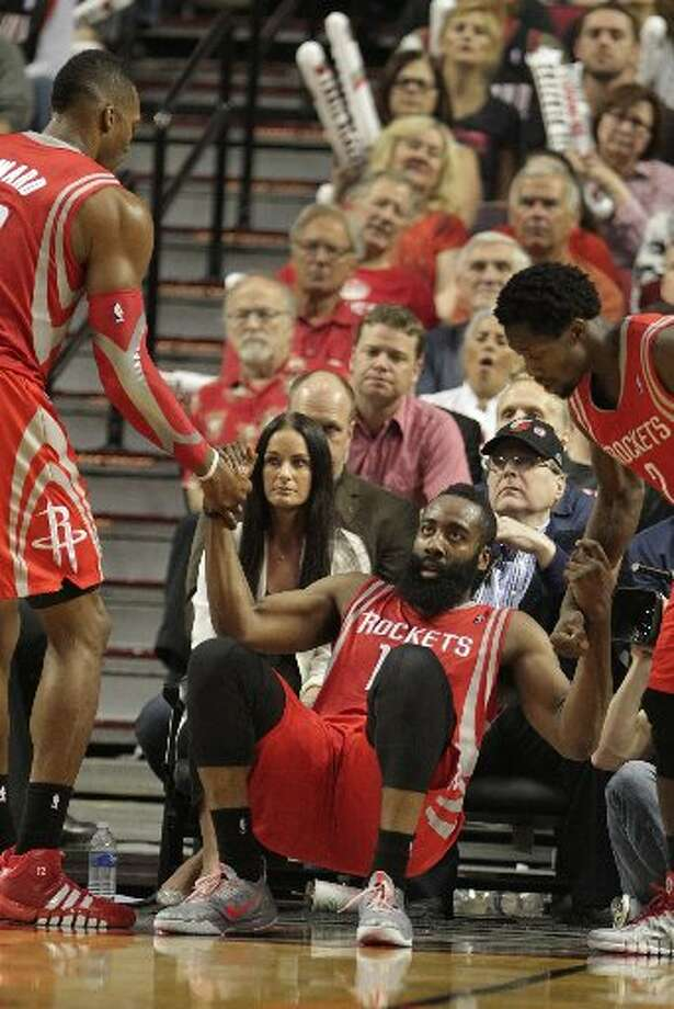 Rockets guard James Harden (13) is helped off the floor by center Dwight Howard (12) and guard Patrick Beverley (2) during the third quarter. Photo: James Nielsen, Houston Chronicle