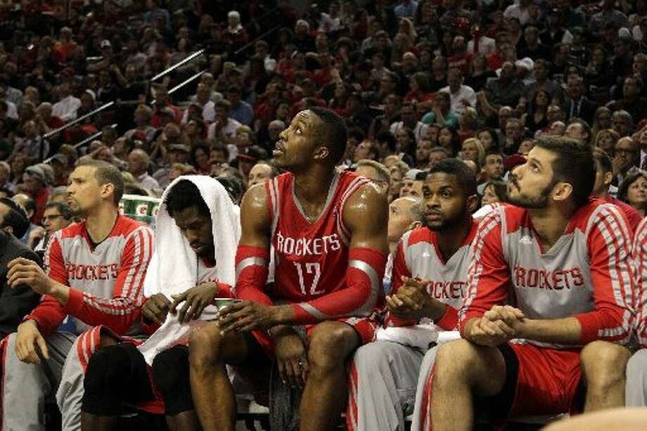 Rockets center Dwight Howard, center, looks up at the scoreboard as he sits on the bench during the third quarter. Photo: James Nielsen, Houston Chronicle