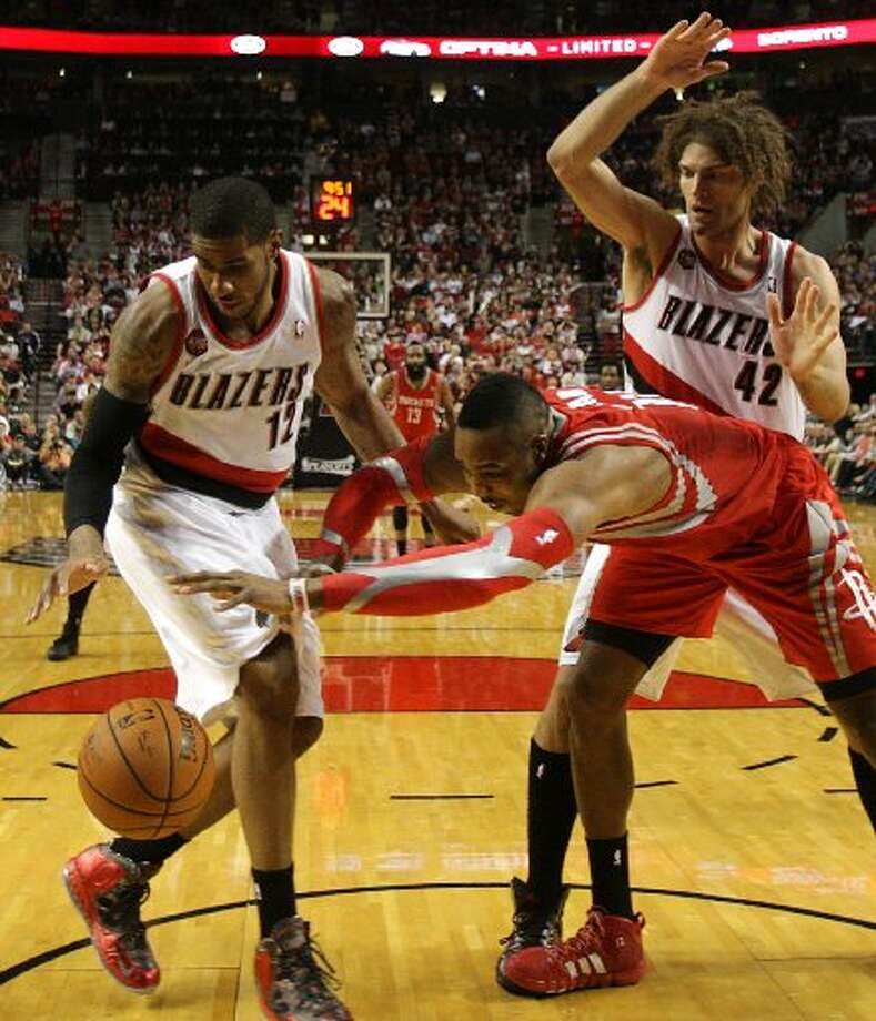 Trail Blazers forward LaMarcus Aldridge (12), Houston Rockets center Dwight Howard, center, and Portland Trail Blazers center Robin Lopez (42) go after a loose ball. Photo: James Nielsen, Houston Chronicle