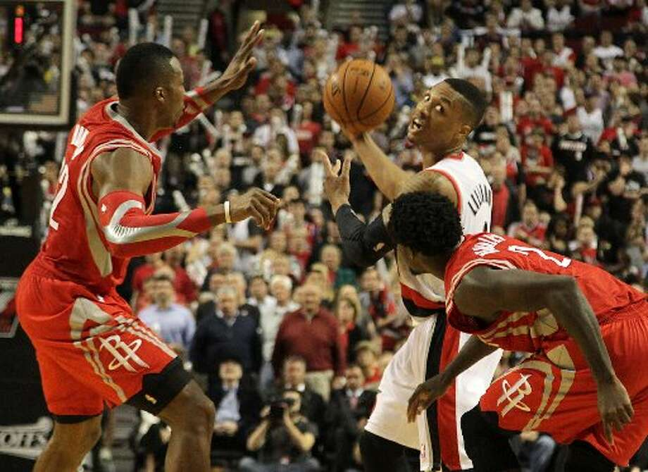 Trail Blazers guard Damian Lillard (0) is defended by Houston Rockets center Dwight Howard (12) and guard Patrick Beverley (2) during the fourth quarter. Photo: Houston Chronicle