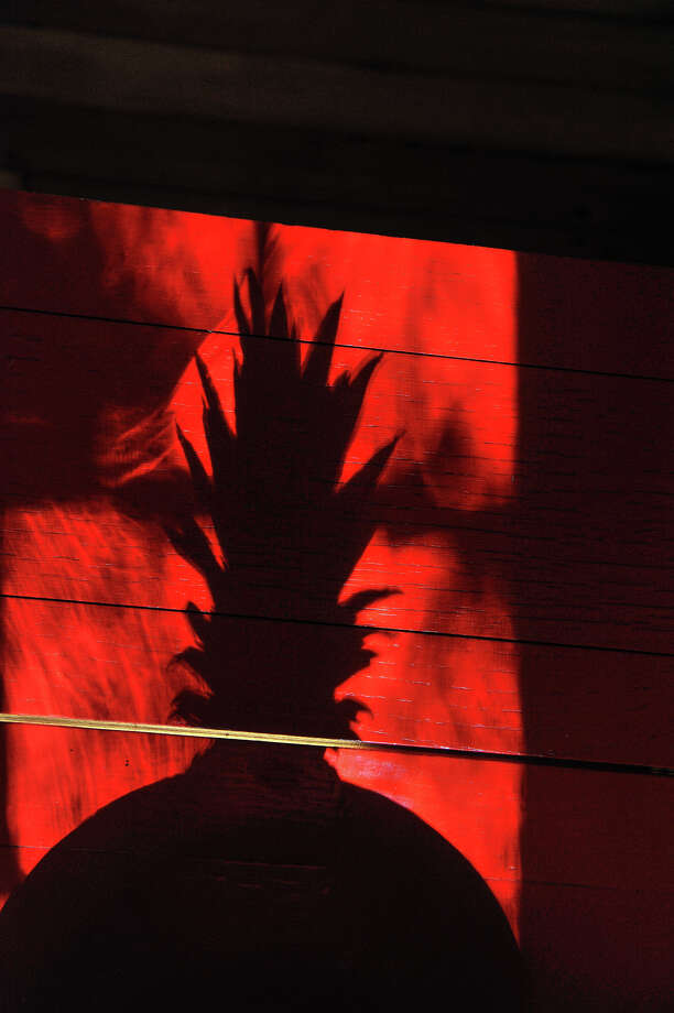 A pineapple casts a shadow on a red breakfast table in the home of Ruthie  Foultz. Photo: Robin Jerstad