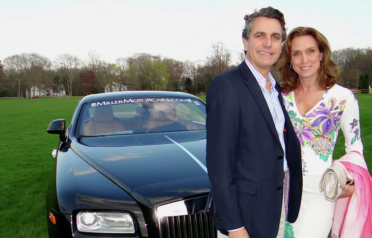 Steve and Joan Panagos of Fairfield with a Rolls Royce at Near & Far Aid's Toast the Tour reception.