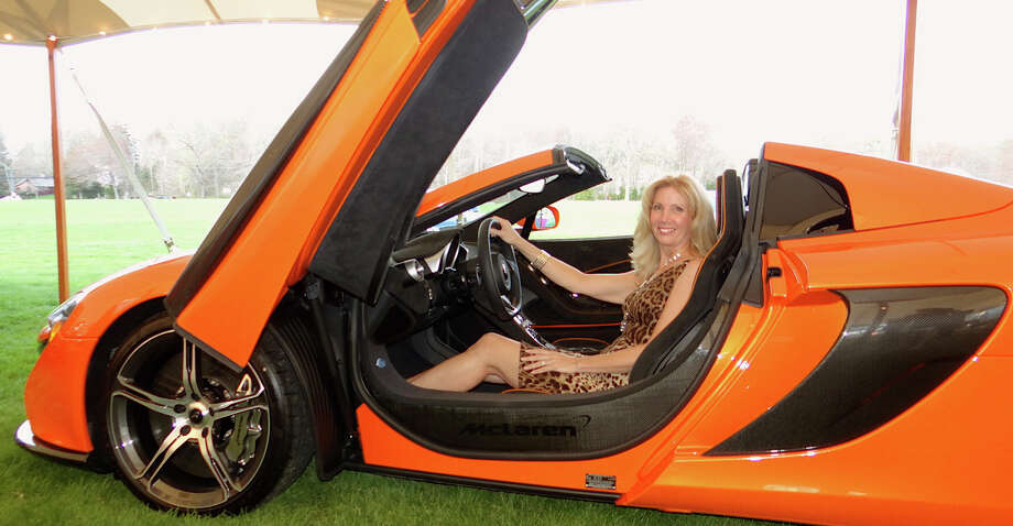 Gina Manoni, a Near & Far Aid board member, in a 2015 McLaren 650S Spider at the group's Toast the Tour event at the Fairfield County Hunt Club. Photo: Mike Lauterborn / Westport News