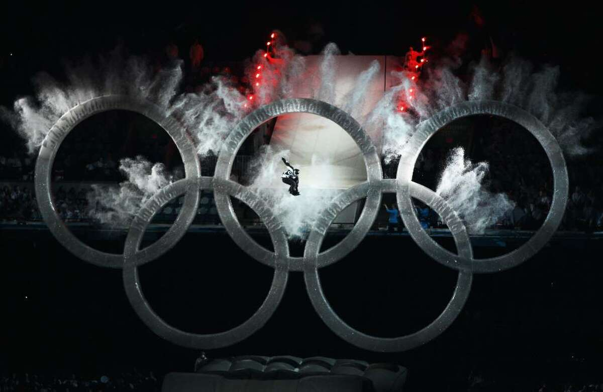 VANCOUVER, BC - FEBRUARY 12: A snowboarder jumps through the Olympic rings to kick off the Opening Ceremony of the 2010 Vancouver Winter Olympics at BC Place on February 12, 2010 in Vancouver, Canada. (Photo by Matthew Stockman/Getty Images)