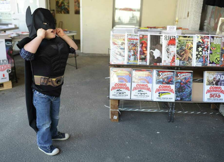 Lleyton Wilder, 4, of Bethel, adjusts his Batman mask while browsing comics at Comic Underground in Bethel, Conn. for Free Comic Book Day Saturday, May 3, 2014.  Patricipating comic stores around the world give away free comic books on the first Saturday of May every year for Free Comic Book Day.  Comic Underground in Bethel also had discounts on certain items along with coloring and trivia sheets for children. Photo: Tyler Sizemore / The News-Times