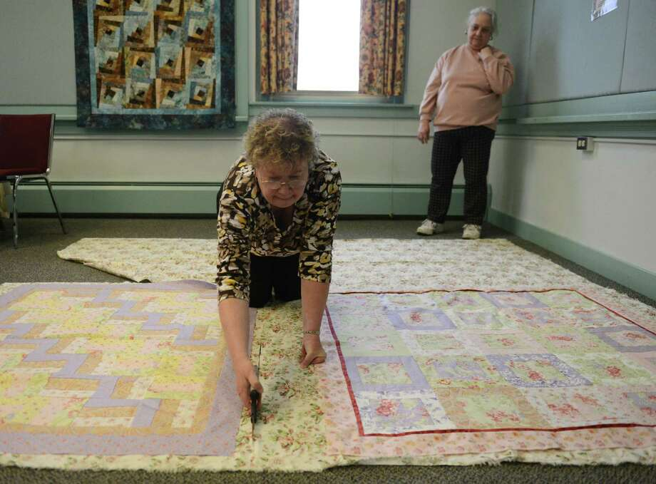 Veralyn Davee cuts the quilt backing around the front design during the weekly quilting circle at Richmond Senior Center in New Milford, Conn. Tuesday, April 29, 2014.  The group, formed in 2006, meets every Tuesday to work on individual and group quilting projects.  There group's 12 members often donate their finished work, including recent donations to Harrybrooke Park, the Newtown Survivors Project and Ann's Place. Photo: Tyler Sizemore / The News-Times