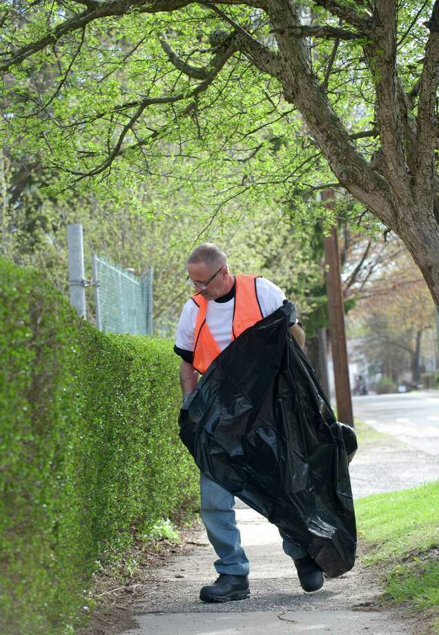 Rick Bloom, 55, of Danbury, picks up trash along Spring Street in Danbury, Conn, while taking part in a volunteer-to-work program by Jericho Partnership, of Danbury. Participants in the program took part in Clean City Day on Saturday, May 3, 2014. The program could lead to a long term transitional work program that would include job training, job placement and job coaching for the homeless.  Jericho Partnership is a collaboration of ministries and congregations serving the youth, homeless and other at-risk populations of Danbury. Photo: H John Voorhees III / The News-Times Freelance