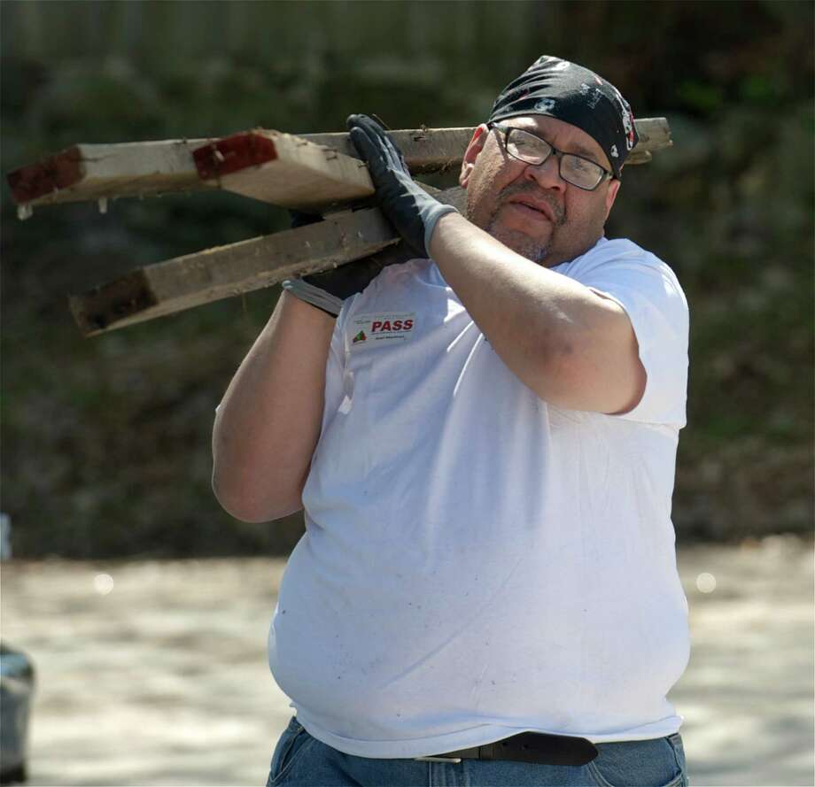 Alex Martinez, 50, of Stamford, a participant in Jericho Partnership's volunteer-to-work program, carries part of an old fence to the curb, at St Paul Lutheran Church on Spring Street,  as part of Clean City Day, in Danbury, Conn.  Participants worked with Jericho staff and volunteers as part of a program that could lead to a long term transitional work program that would include job training, job placement and job coaching for the homeless. Jericho Partnership is a collaboration of ministries and congregations serving the youth, homeless and other at-risk populations of Danbury. Photo: H John Voorhees III / The News-Times Freelance