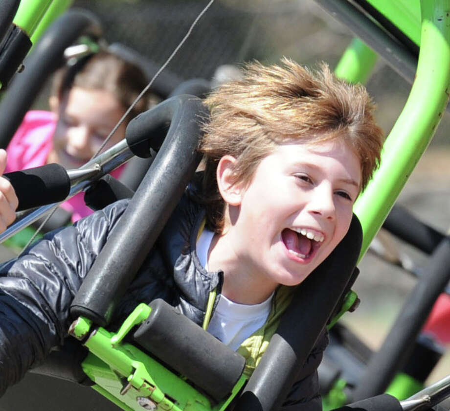 "Bonorino Segundo, 9, of Greenwich, reacts to the force of gravity while on an amusement ride during the annual North Mianus School carnival and PTA fundraiser known as the ""Pow Wow, "" at the school in Greenwich, Conn., Saturday, May 3, 2014. Photo: Bob Luckey / Greenwich Time"