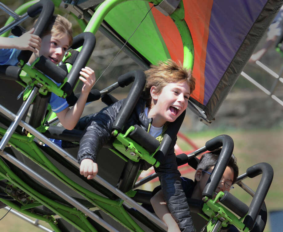"At center, Bonorino Segundo, 9, of Greenwich, reacts to the force of gravity while on an amusement ride during the annual North Mianus School carnival and PTA fundraiser known as the ""Pow Wow, "" at the school in Greenwich, Conn., Saturday, May 3, 2014. Photo: Bob Luckey / Greenwich Time"