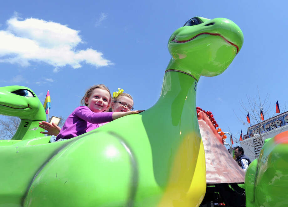 """From left, Ellie Englund, 7, and Mara Visentin, 6, both of Greenwich, enjoy the Dino-Ride during the annual North Mianus School carnival and PTA fundraiser known as the """"Pow Wow, """" at the school in Greenwich, Conn., Saturday, May 3, 2014. Photo: Bob Luckey / Greenwich Time"""