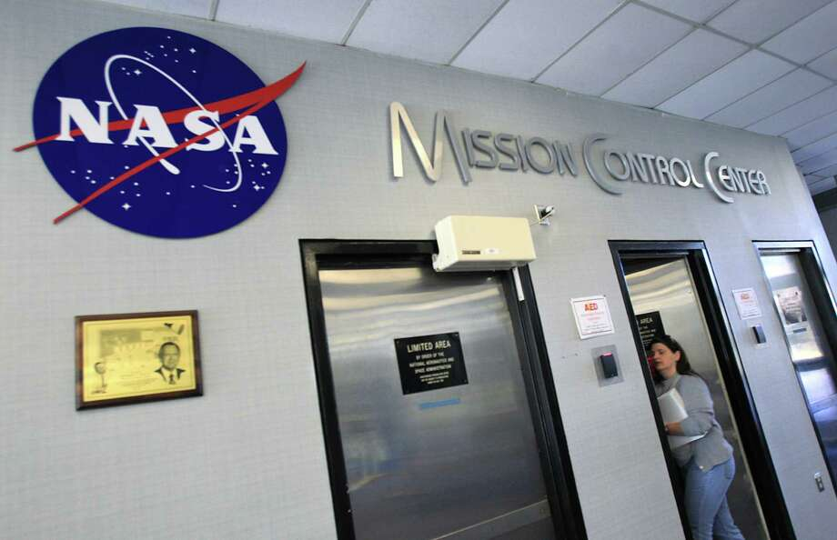NASA officials monitor and lead the operations of the multinational crew onboard the  International Space Station from behind this secured entrance to the Mission Control Center at Johnson Space Center. Photo: Mayra Beltran, Staff / © 2013 Houston Chronicle