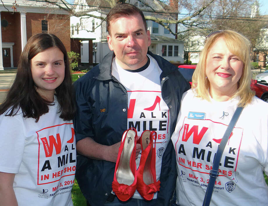 Police Chief Gary MacNamara holding his red stilettos, is flanked by daughter, Cassidy, 12, left, and Debra Greenwood, CEO of the Center for Family Justice, at the group's 2nd annual Walk a Mile in Her Shoes fundraiser Saturday. Photo: Mike Lauterborn / Fairfield Citizen