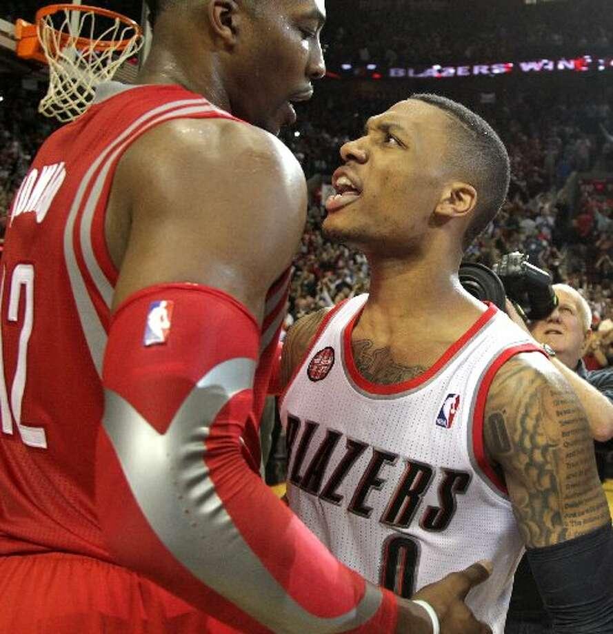 Rockets center Dwight Howard (12) and Portland Trail Blazers guard Damian Lillard (0) meet on the court after Lillard hit the game-winning shot. Photo: James Nielsen, Houston Chronicle