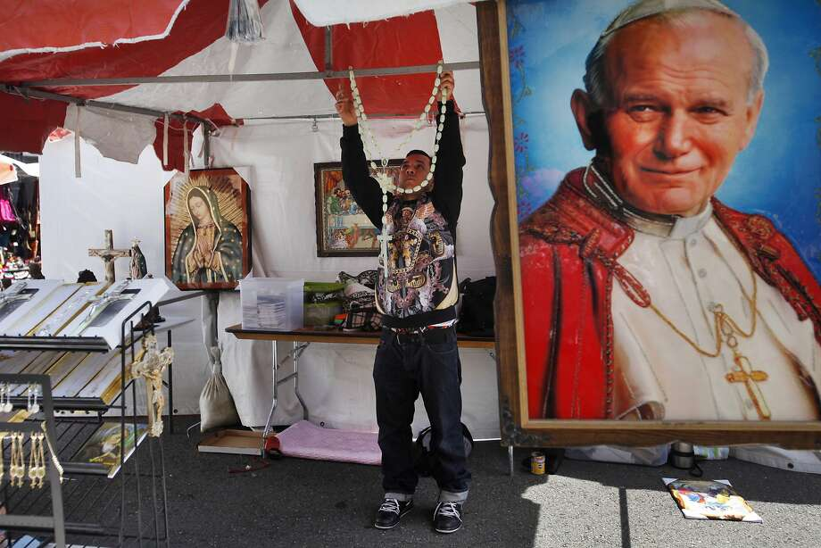 Luis Ledesma hangs up a rosary in the booth he and his wife run at the Cinco de Mayo festival, Sweet Angel. Photo: Leah Millis, San Francisco Chronicle